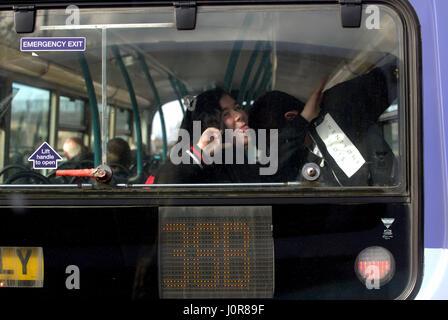 Kids Messing About Facce di trazione al posteriore di un autobus tamponando Foto Stock