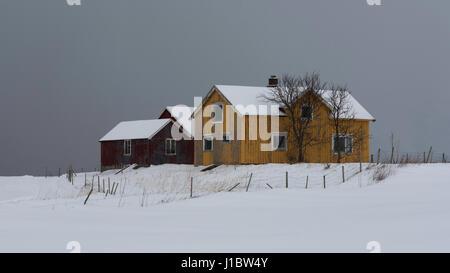 Casa colonica di colore giallo e rosso dépendance nella neve nei pressi di Flakstad chiesa su Flakstadoya, Isole Foto Stock
