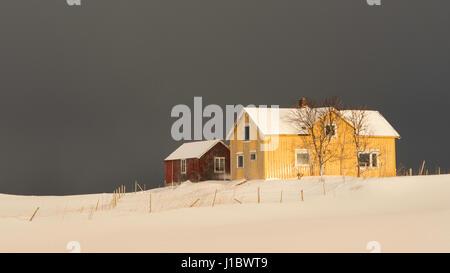 Casa Gialla e rossa dépendance in presenza di neve nei pressi di Flakstad Chiesa su Flakstadoya, Isole Lofoten in Foto Stock