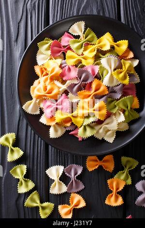 Materie italiano farfalle multicolori pasta close-up sul tavolo. Vista verticale da sopra Foto Stock