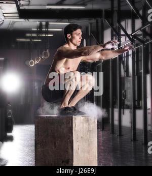 Montare il giovane uomo box jumping in una palestra crossfit.atleta è performin Foto Stock