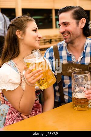 Coppia giovane in tradizionali bavaresi Tracht - Dirndl e lederhosen - in una tenda di birra al Oktoberfest godendo Foto Stock