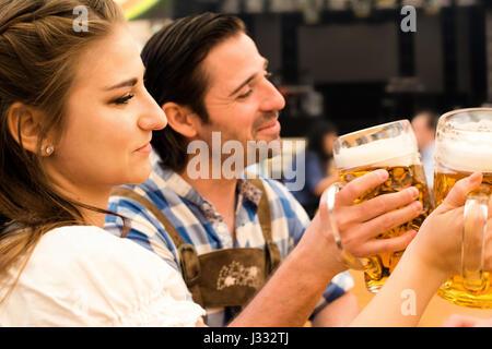Coppia giovane in tradizionali bavaresi Tracht - Dirndl e lederhosen - in una tenda di birra al Oktoberfest a Monaco Foto Stock