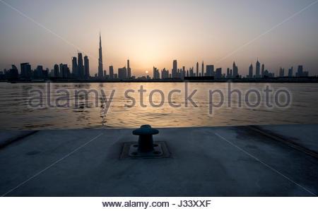 Silhouette di Dubai durante un bel tramonto sulla città, vista dal canale d'acqua con gancio di ancoraggio in primo Foto Stock