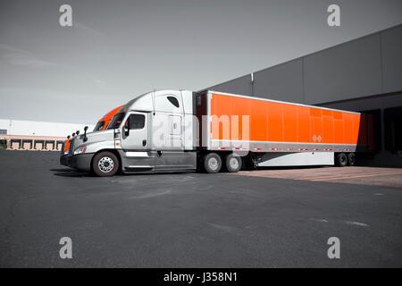 Due moderni commerciale professionale semi carrelli in grigio e arancione con dry van rimorchi sono in piedi nel Foto Stock