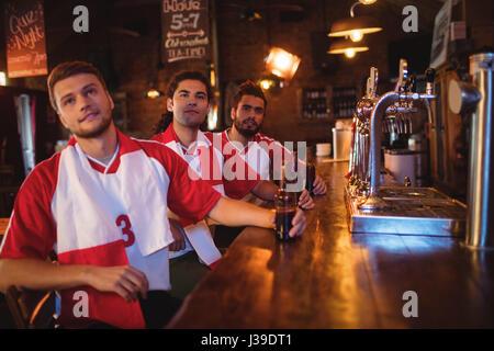 Gruppo di amici maschi guardando la partita di calcio in pub Foto Stock