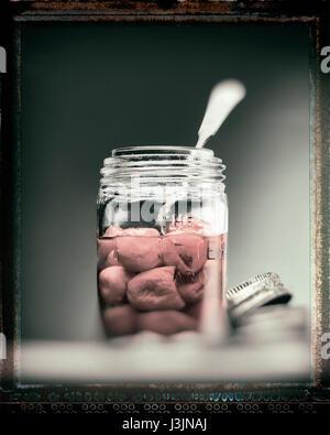 I peperoni in un vasetto di vetro con un cucchiaio Foto Stock