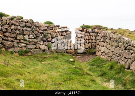 Un squeeze stile in pietra a secco muro costruito da blocchi di granito di diverse dimensioni e colori a Cape Cornwall, Foto Stock