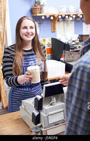 Cameriera In Cafe che serve il cliente con il caffè da asporto Foto Stock
