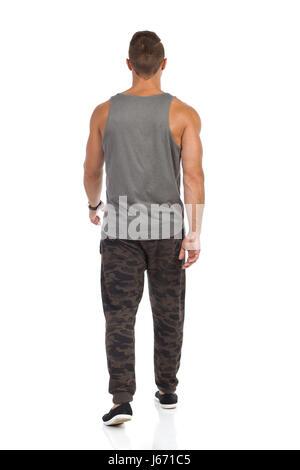 Montare l uomo a camminare in tuta con pantaloni camo, grigio serbatoio superiore e nero sneakers. Vista posteriore. Foto Stock