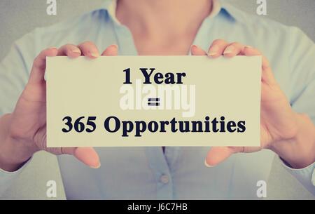 Closeup imprenditrice mani carta bianca segno con un anno 365 opportunità di messaggio di testo isolato sul muro Foto Stock