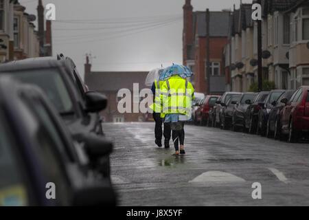 Giovane a piedi sotto la pioggia in mezzo alla strada su un umido molto pomeriggio. Foto Stock