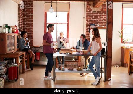 Cinque amici appendere fuori in un caffè in cucina a piena lunghezza Foto Stock