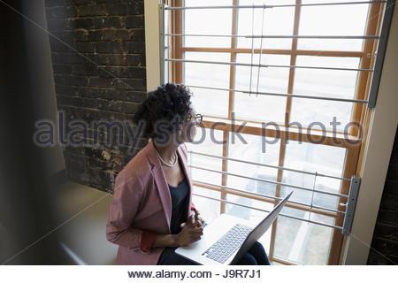 Malinconici imprenditrice creativo con il computer portatile a guardare fuori dalla finestra la tromba delle scale Foto Stock