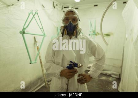 Ritratto di pittore azienda pistola di verniciatura a spruzzo indossando maschera a gas in officina biciclette Foto Stock