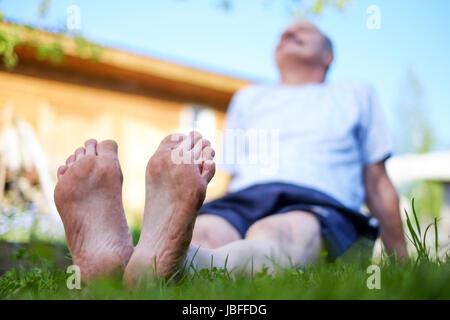 Uomo che stabilisce il campo d'erba. Egli relax nella natura in estate. Cercare su sky Foto Stock