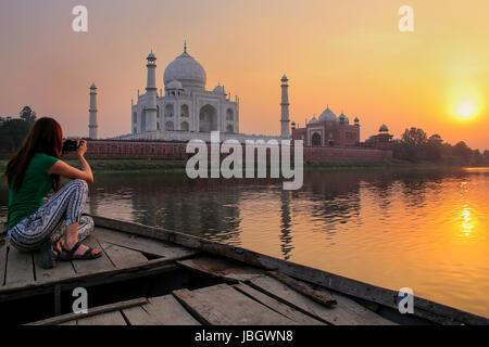 Donna guardando il tramonto Taj Mahal da una barca, Agra, India. Esso fu costruito nel 1632 dall'imperatore Shah Foto Stock