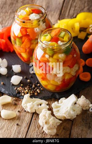 In casa piccante Giardiniera sottaceto con peperoni, carote e cavolfiore close-up in vasetti di vetro. In verticale Foto Stock
