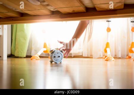 Primo piano della giovane donna di raggiungere sotto il letto e premendo il tasto snooze sulla sveglia Foto Stock