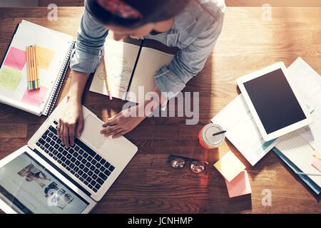 Da sopra il giovane imprenditore donna seduta e la digitazione di un laptop sul posto di lavoro in ufficio. Foto Stock