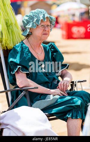 Senior donna, 60s, in stile vittoriano verde il costume da bagno, seduti su una sedia sulle sabbie a Broadstairs Foto Stock
