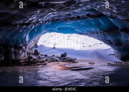 Un uomo è incorniciato dall ingresso di una grande grotta di ghiaccio nei pressi del capolinea della Augustana ghiacciaio Foto Stock
