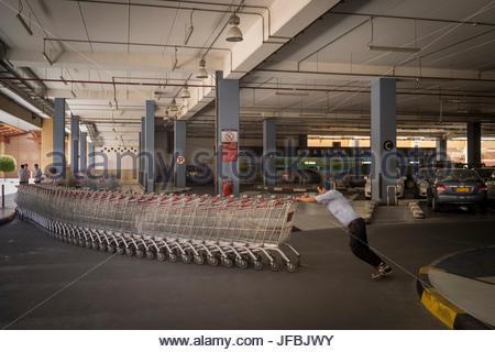 Un uomo spinge i carrelli della spesa nel garage di un centro commerciale di Al Seeb. Foto Stock