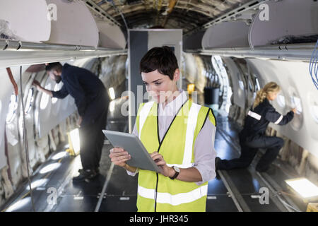 Aeromobili femmina tecnico di manutenzione utilizzando digitale compressa in un aeromobile a compagnie aeree impianto Foto Stock