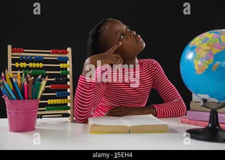 Riflessivo schoolgirl libro di lettura su sfondo nero Foto Stock