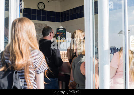 I clienti in attesa all'interno di un pesce e chip shop in Margate, Kent. Foto Stock