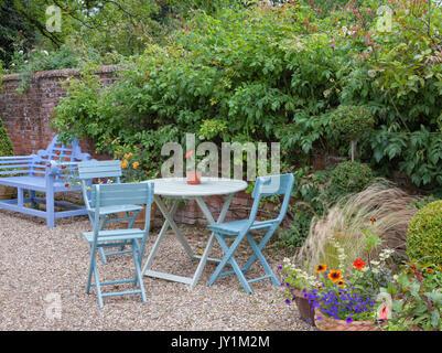 Banco di blu, patio tavolo e sedie da una parete in un cottage Inglese giardino, estate . Foto Stock