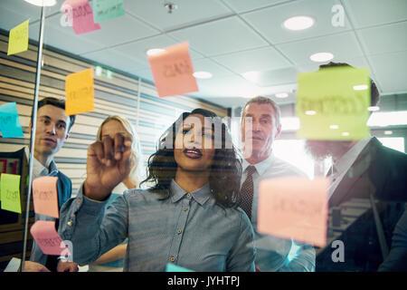 Gruppo di imprenditori il brainstorming con la donna in primo piano, mettendo una nota adesiva sul vetro Foto Stock
