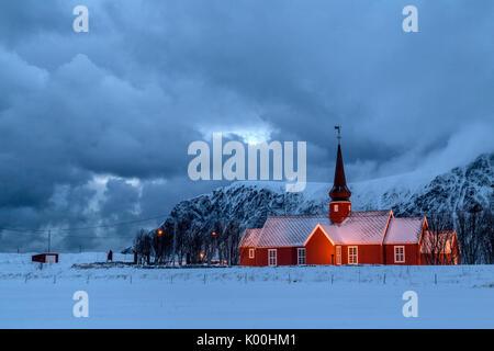 Luci su la Chiesa al tramonto con le vette dolomitiche innevate sullo sfondo Flakstad Isole Lofoten in Norvegia Foto Stock
