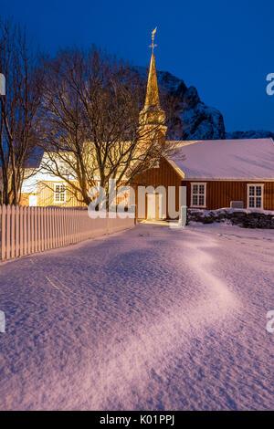 Le luci sulla tipica chiesa in legno circondato da neve Flakstad Isole Lofoten Norvegia del Nord Europa Foto Stock