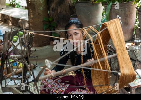 Una giovane donna Lao spin con filati di seta in Xhang Khong village. Conoscenza della produzione di tessuti di Foto Stock