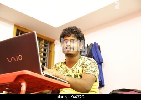 Smiley giovane con laptop a tavola Foto Stock