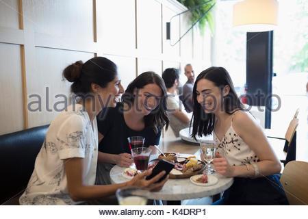 Donna sorridente gli amici a bere vino e utilizzando il telefono cellulare presso il cafe tabella Foto Stock