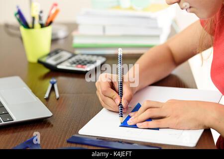 Giovani schoolgirl sta facendo i compiti con la matematica e la geometria accanto a un computer portatile, calcolatrice Foto Stock