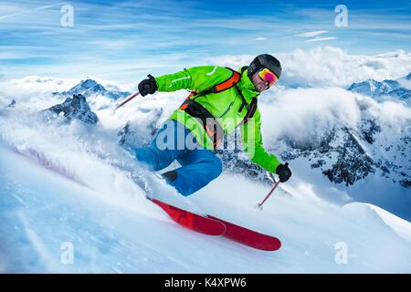 Sorprendente colpo di un colorato vestito con rifiniture a sciare sulla neve onda. Foto Stock
