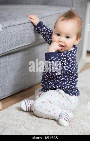Nove mesi baby ragazza seduta sul pavimento da divano Foto Stock