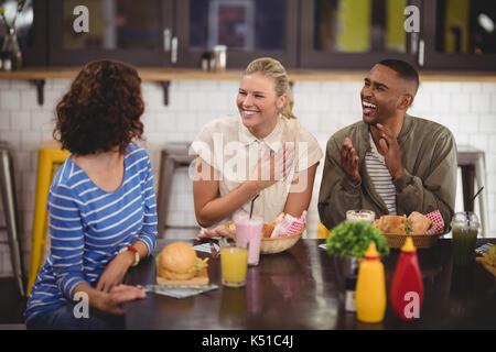 Allegro giovani amici di parlare mentre è seduto con cibi e bevande a tavola in coffee shop Foto Stock