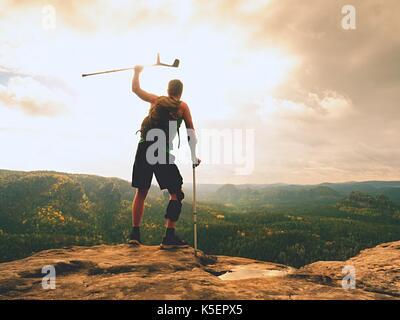Uomo con le stampelle e la gamba rotta fissata in ortesi per ginocchio caratteristica.traveler con gamba ferito Foto Stock