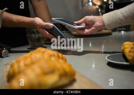 La donna il pagamento fattura tramite lo smartphone utilizzando la tecnologia NFC in ristorante Foto Stock