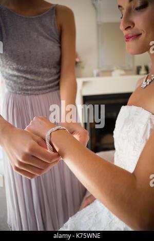 Sezione mediana della damigella assistere sposa di vestirsi in sala di montaggio Foto Stock