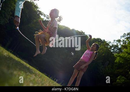 La madre e le figlie giocando con il salto con la corda al parco durante l'estate Foto Stock