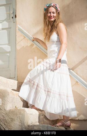 Giovane donna in abito bianco con fiore head band su per le scale Foto Stock