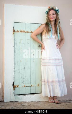 Giovane donna in abito bianco con fiore head band in piedi dalla porta Foto Stock
