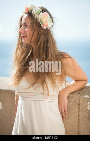 Dettaglio della giovane donna in abito bianco con fiore head band Foto Stock