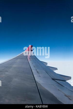 Ala di aereo da aria nel cielo aletta di color rosso con la compagnia aerea blue sky nuvole Foto Stock