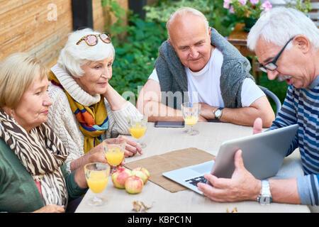 Due coppie senior trascorrere weekend insieme al cortile: essi guardando attraverso le foto sul computer portatile Foto Stock
